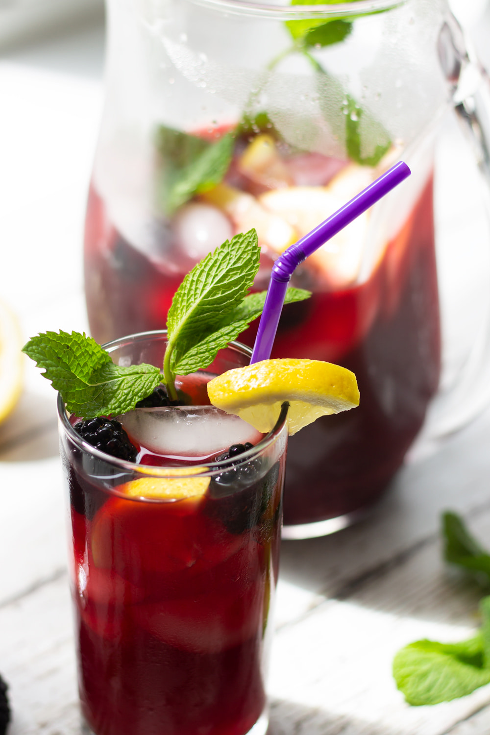 blackberry iced tea in a glass with mint and lemon garnish