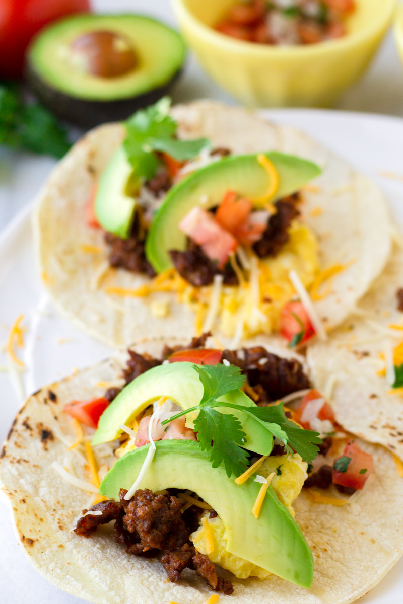 two chorizo and egg breakfast tacos with avocado and pico de gallo
