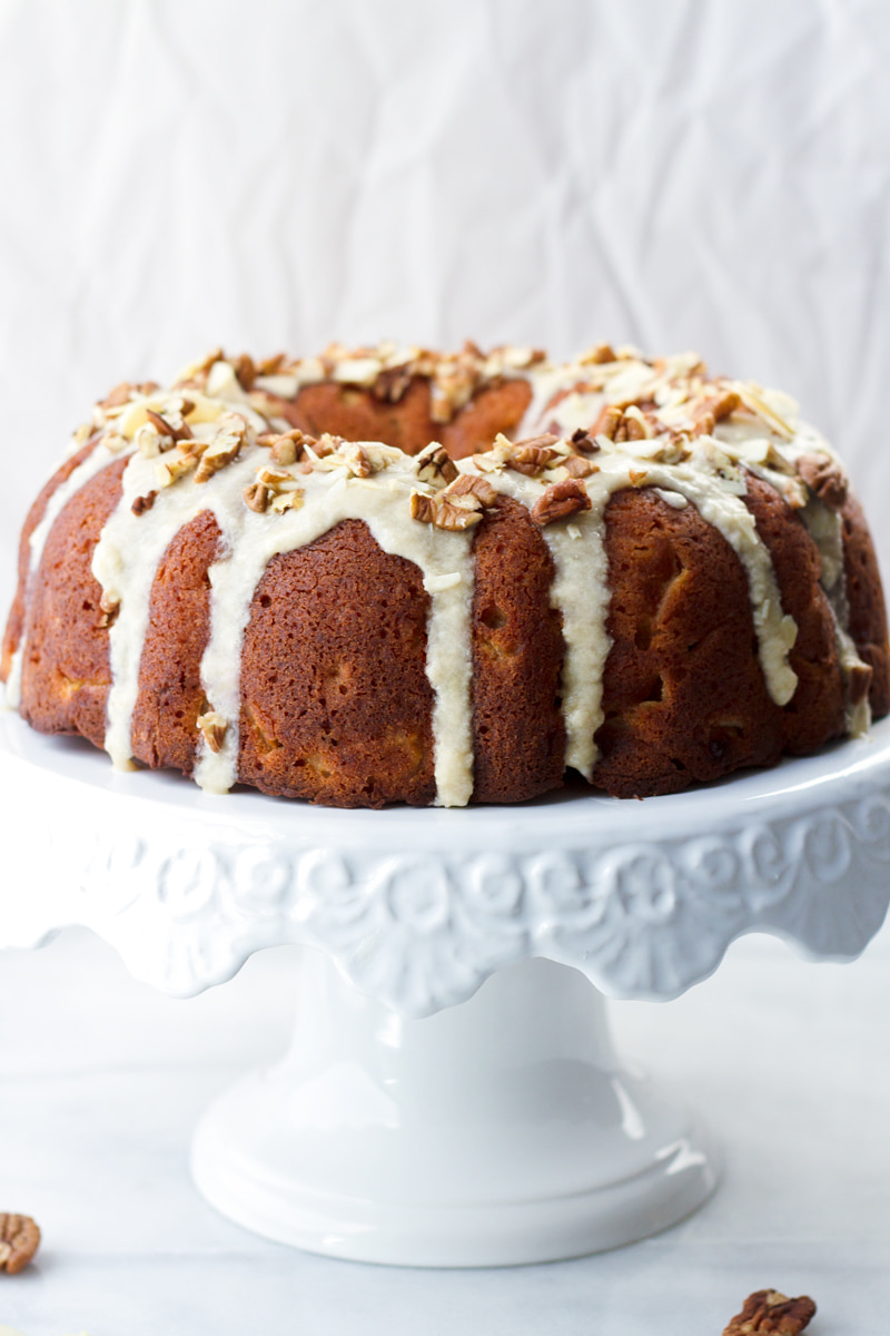 fresh apple bundt cake with glaze on cake stand