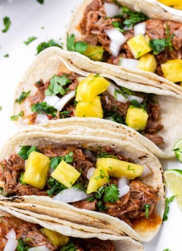 Four Tacos with Al Pastor Meat and Diced Pineapple Stacked in a Row
