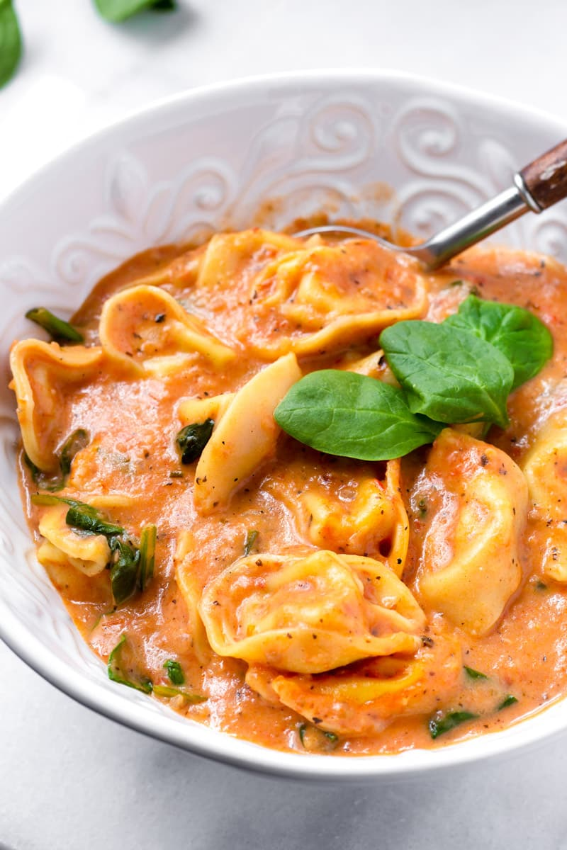 Bowl of Creamy Tortellini Soup with Fresh Spinach Leaves