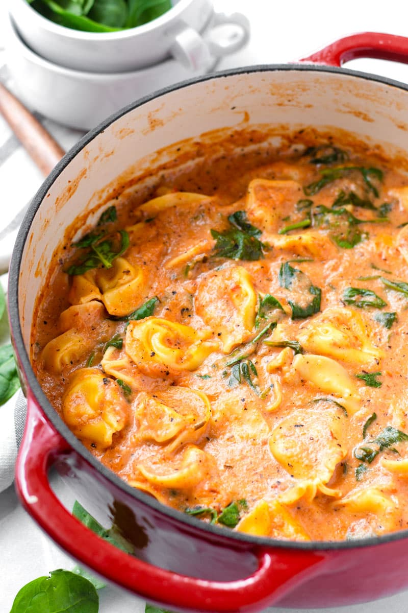 Cheese Tortellini Cooked in the Dutch Oven with Spinach in the Background