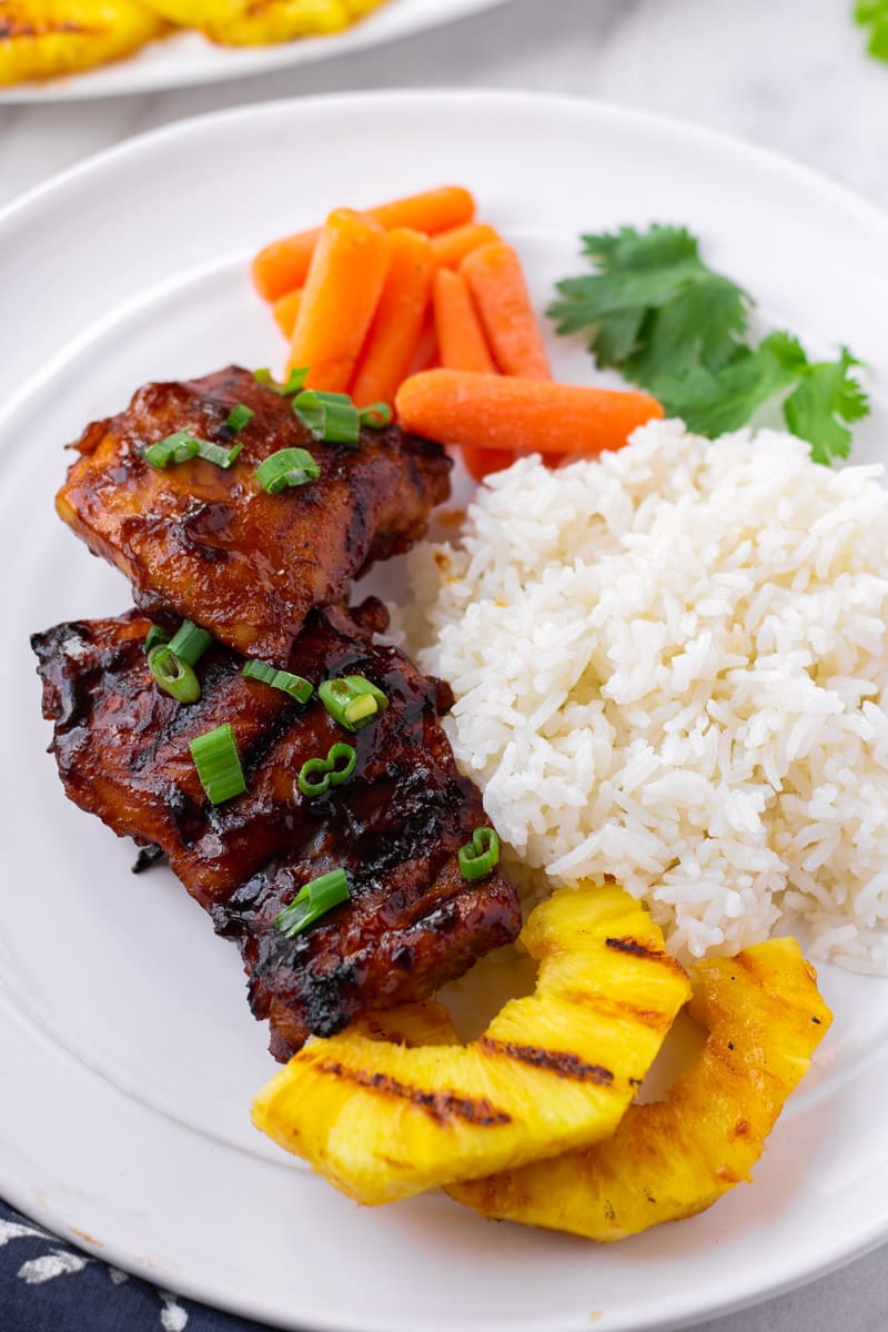 Plate of Grilled Chicken Thighs with Rice, Pineapple, and Carrots