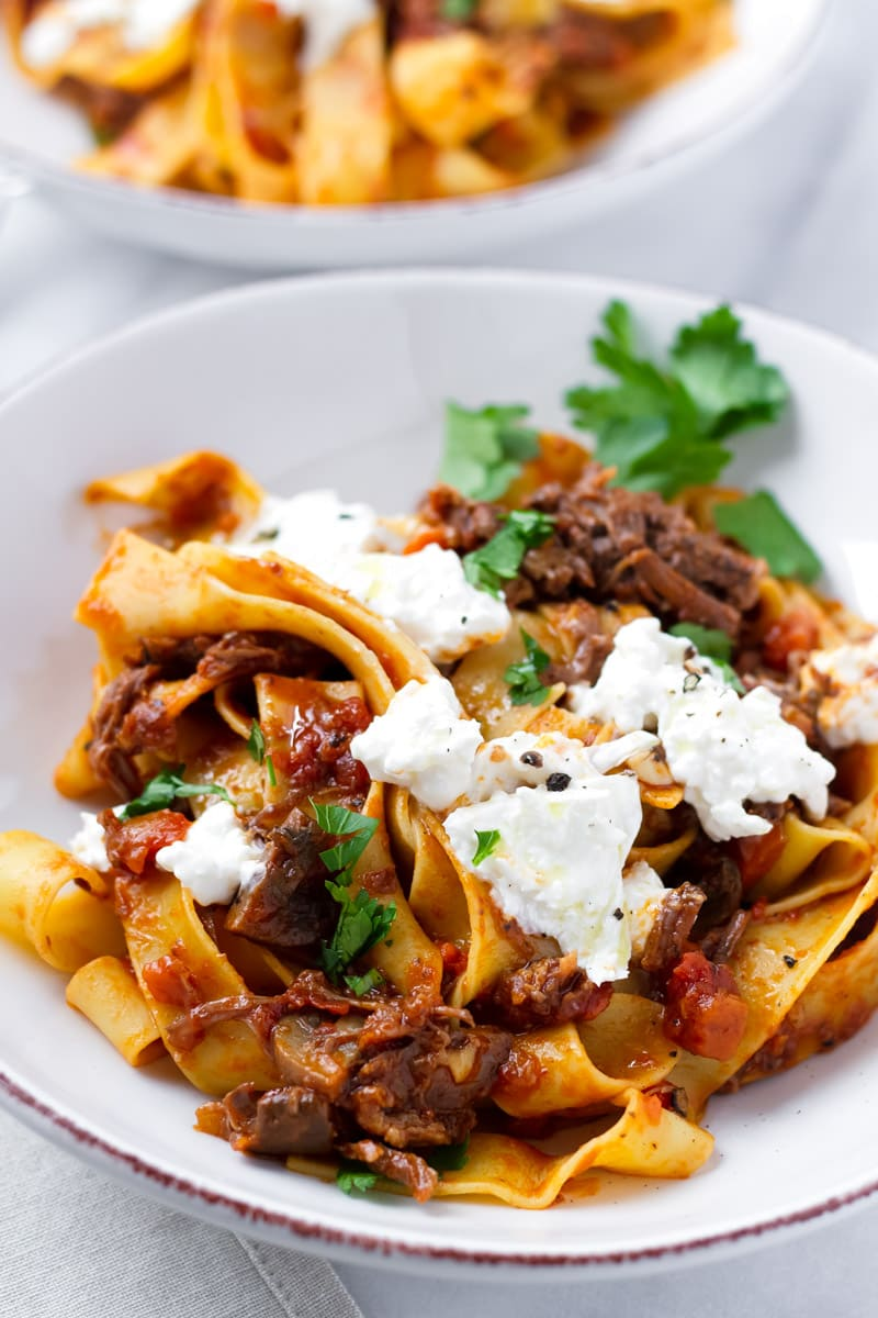 Bowl of Wide Pasta with Slow Cooked Meat Sauce and Topped with Creamy Cheese