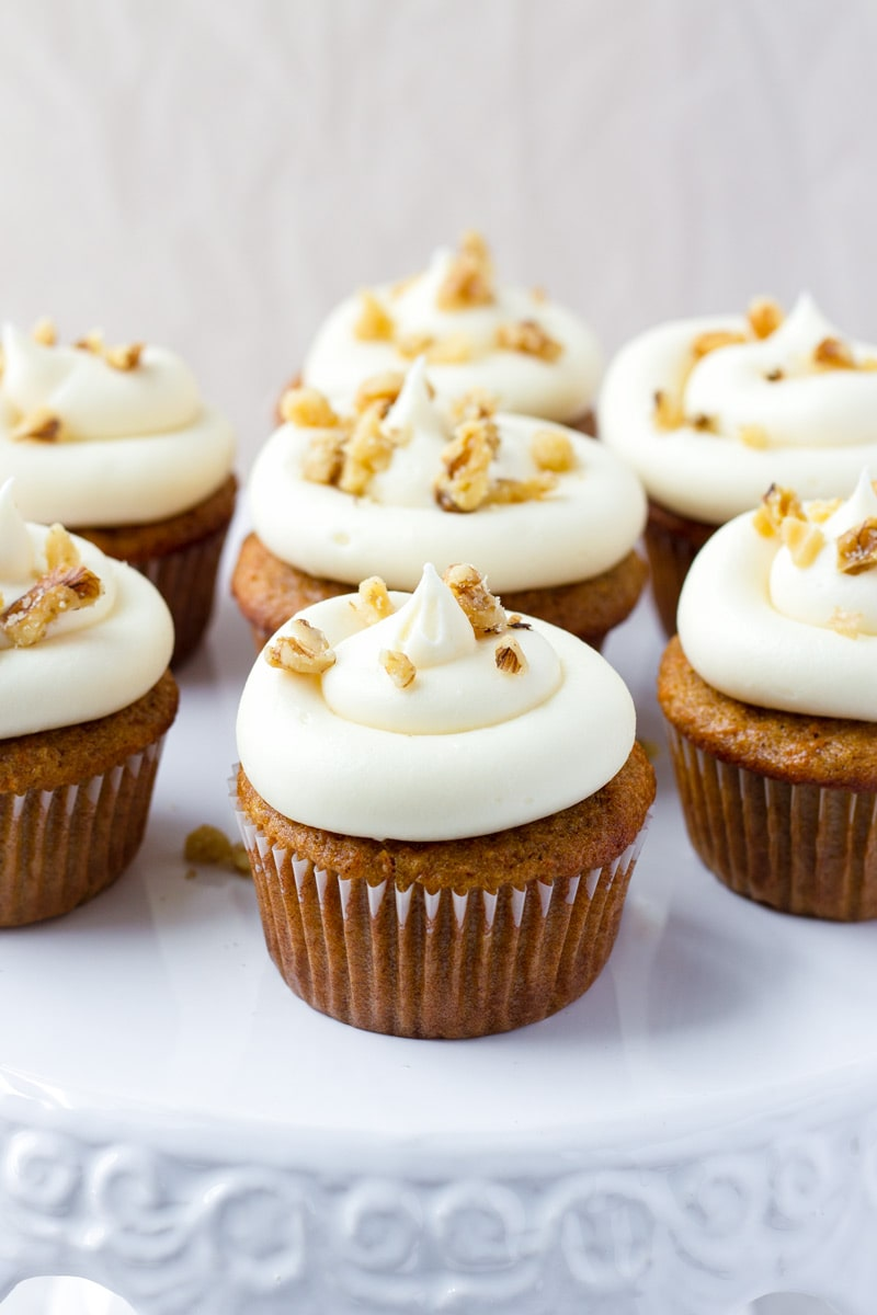 Batch of carrot cake cupcakes on a white cake stand