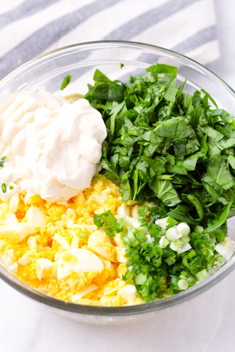 Bowl of chopped eggs, mayonnaise, spinach, scallions, and seasoning
