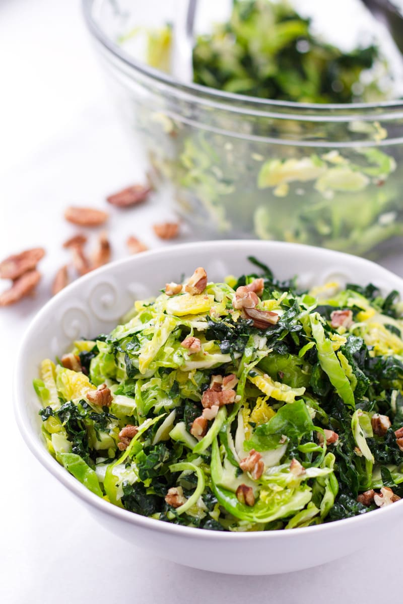 Bowl of brussels sprouts and kale salad with chopped pecans