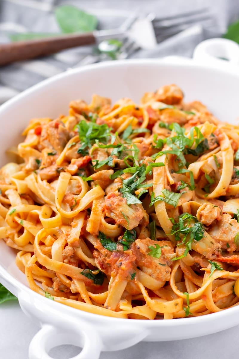 Chicken artichoke pasta with creamy tomato sauce and basil garnish on white bowl