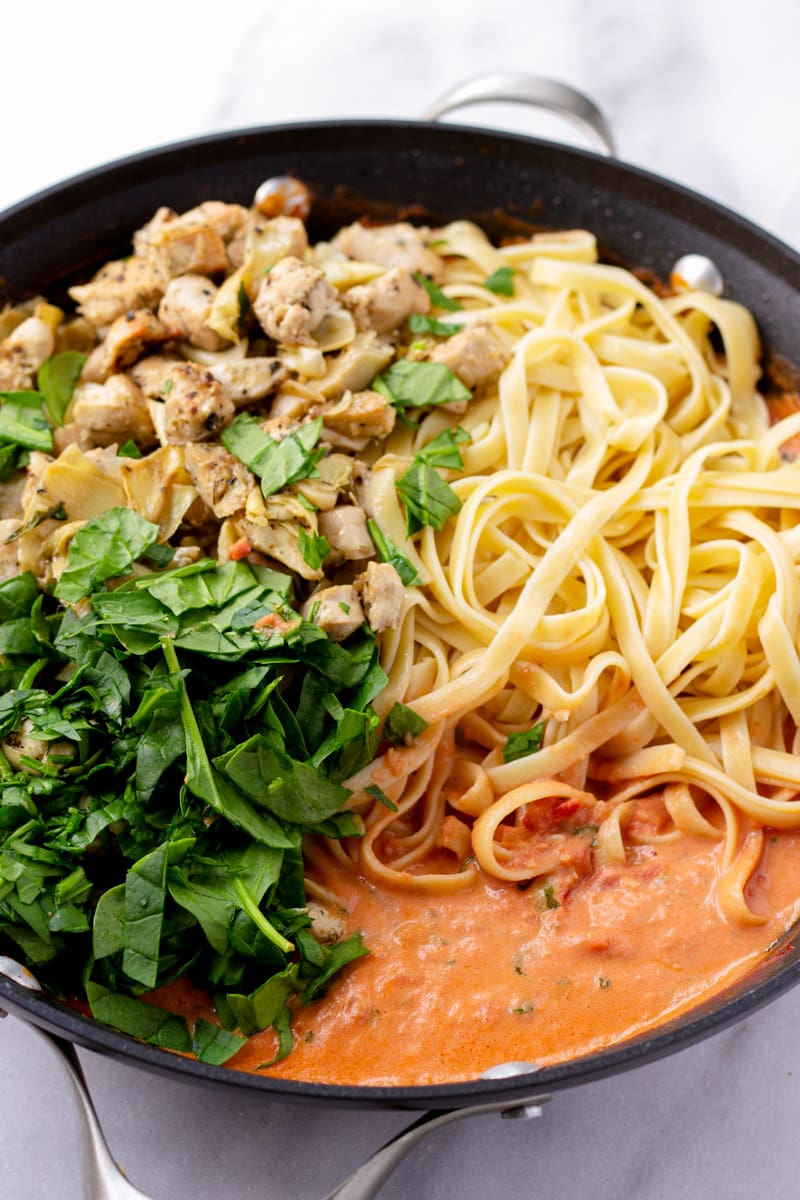 Skillet with ingredients side by side, spinach, chicken, artichokes, pasta, and creamy tomato sauce