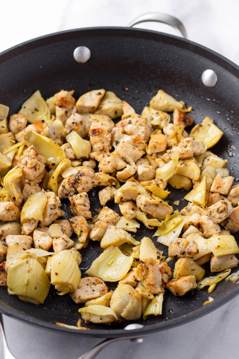Sauteed cubed chicken breasts with artichokes on a non stick skillet