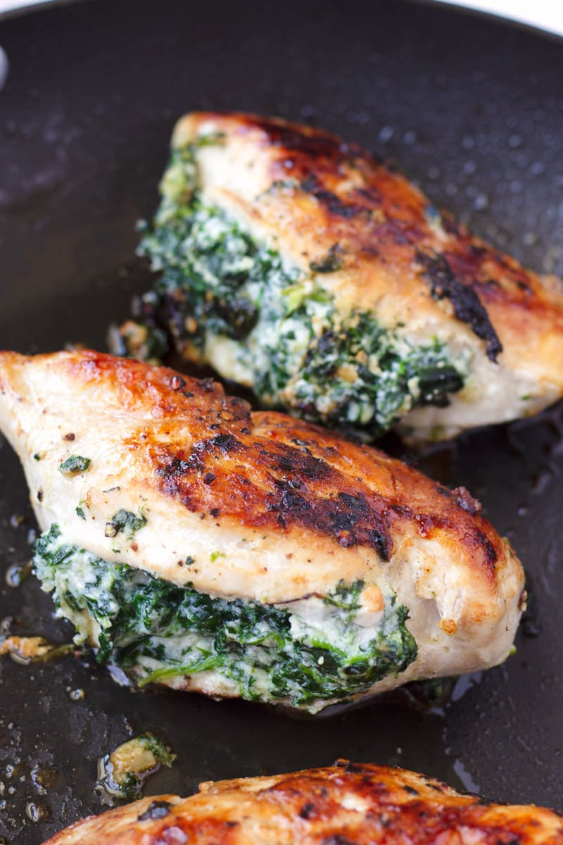 Cooked chicken breasts with spinach filling on a skillet