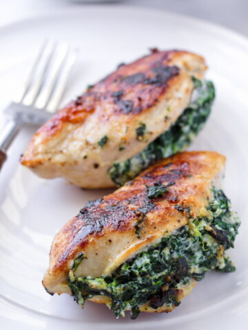 Two pan-seared chicken breasts stuffed with spinach and ricotta on a white plate
