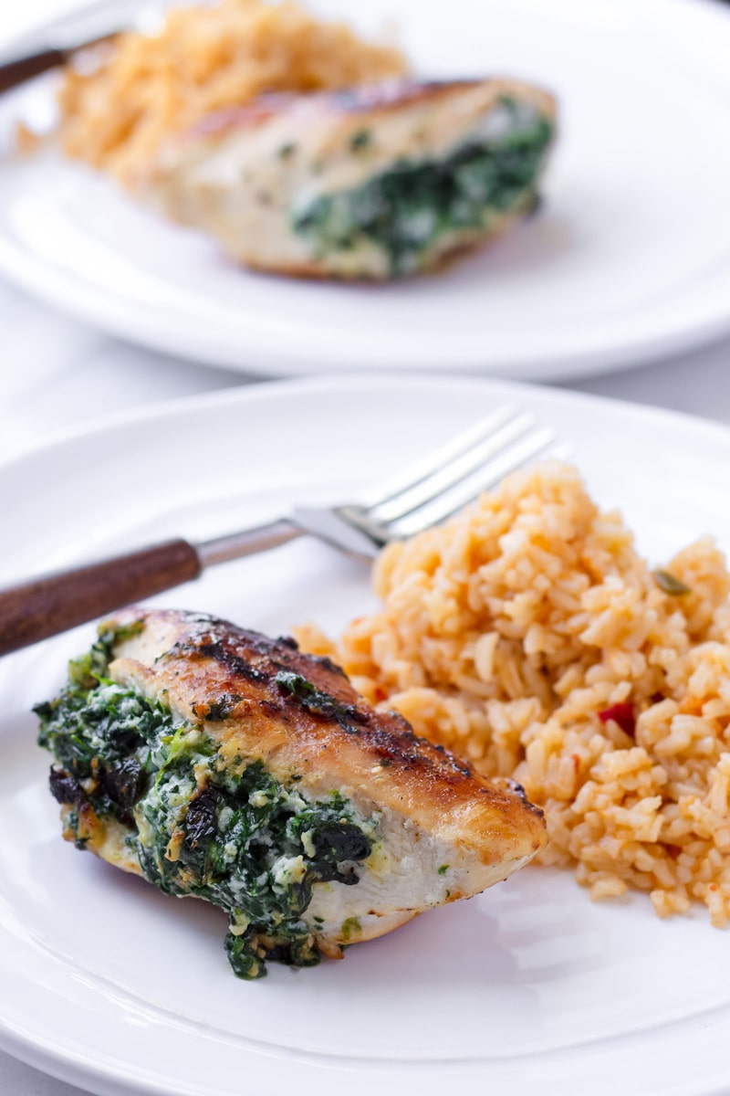 One spinach and ricotta stuffed chicken breast serve with a side of orange rice