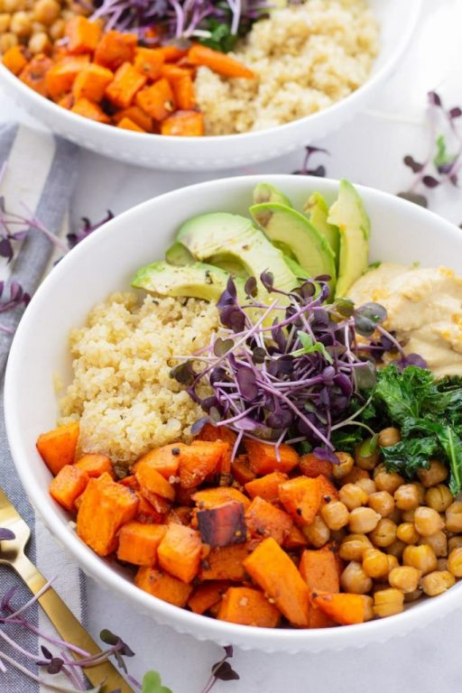 Bowl of sweet potato quinoa bowl with chickpeas, avocado, kale, and hummus