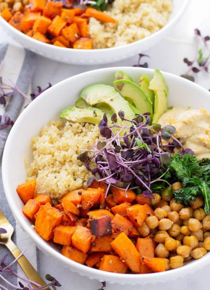 Bowl of sweet potato quinoa bowl with chickpeas, avocado, kale, and hummus
