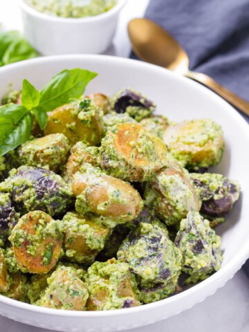 White bowl with pesto potato salad and a golden spoon and pesto sauce in the back