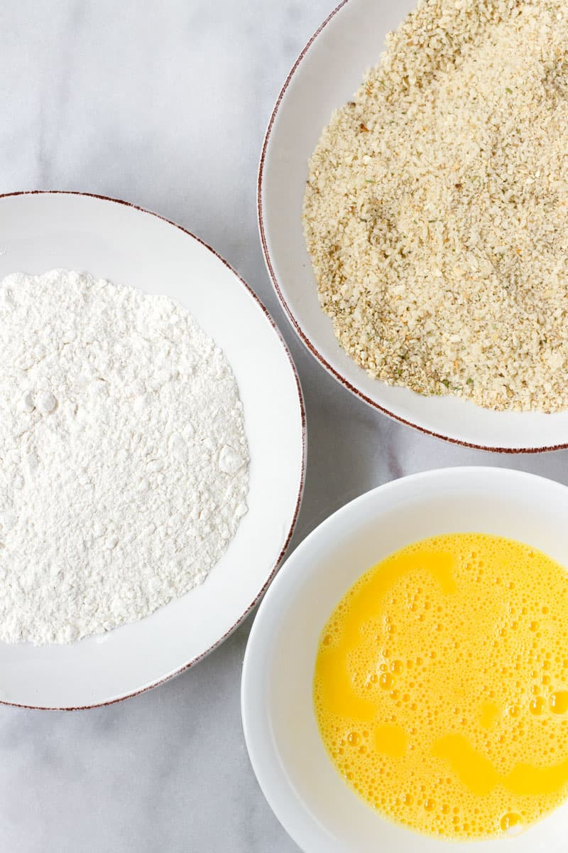 breading station with flour, bread crumbs, and eggs in bowls