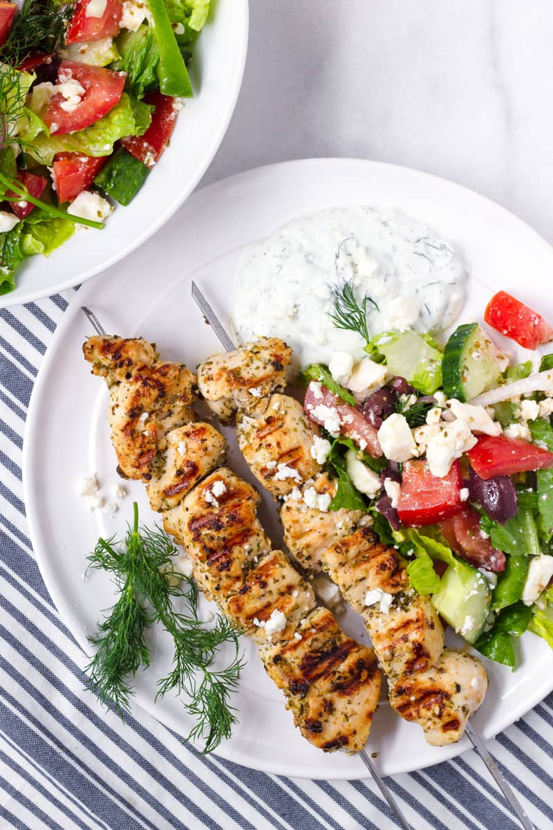 white platter of grilled chicken kabobs on a blue and white striped napkin