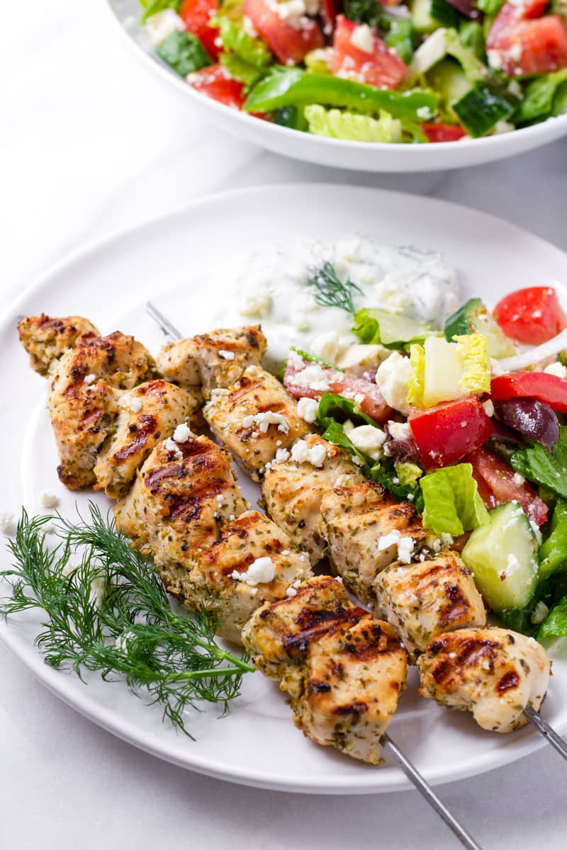 Two Greek style chicken kebabs on a plate with side of Greek salad and tzatziki sauce