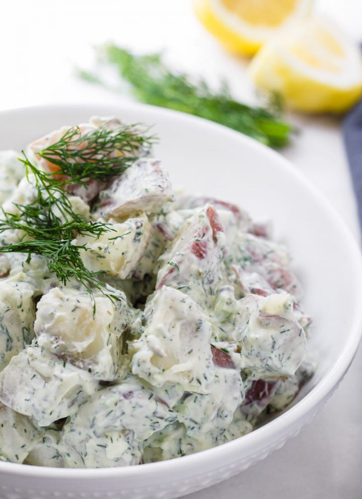 Red potatoes with yogurt and dill dressing in a round bowl