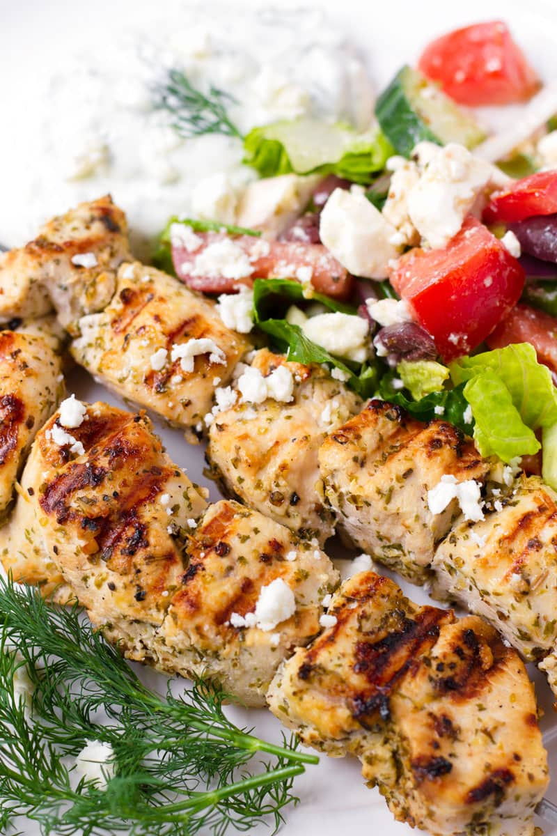 Close up of grilled chicken kabobs with side Greek salad and sprigs of dill as garnish