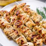 Four Greek chicken skewers on a white plate and with dill garnish