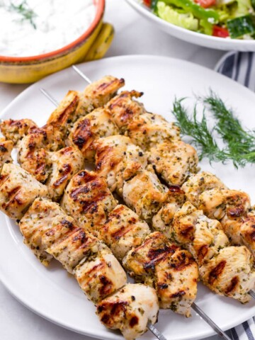 Four chicken kabob skewers on a white plate and tzatziki sauce and salad in the back