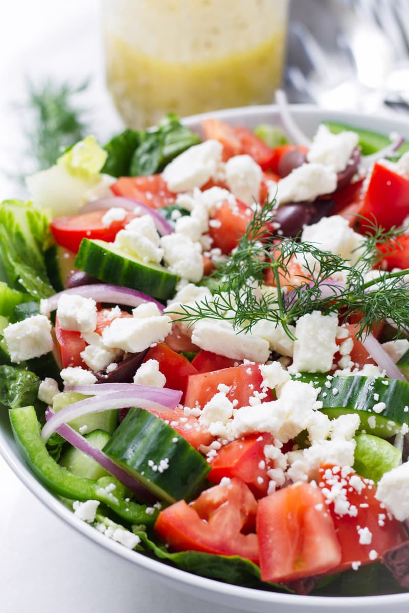 Close up of Greek Salad on white bowl and a mason jar with dressing