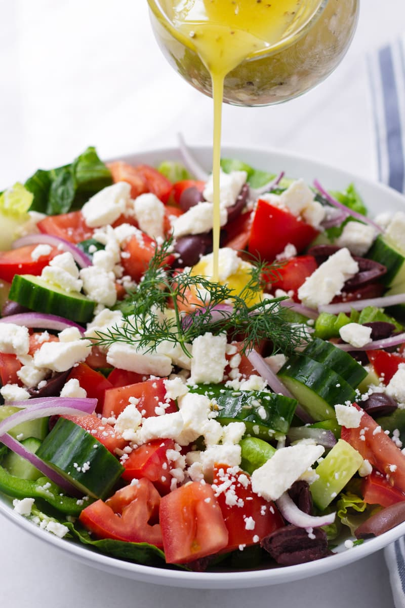 Greek dressing being poured into a a bowl of Greek Salad