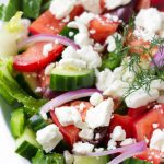 close up of Greek salad with feta crumbles and dill garnish