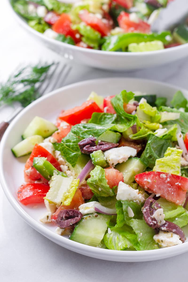 Side portion of Greek style salad on a shallow white plate