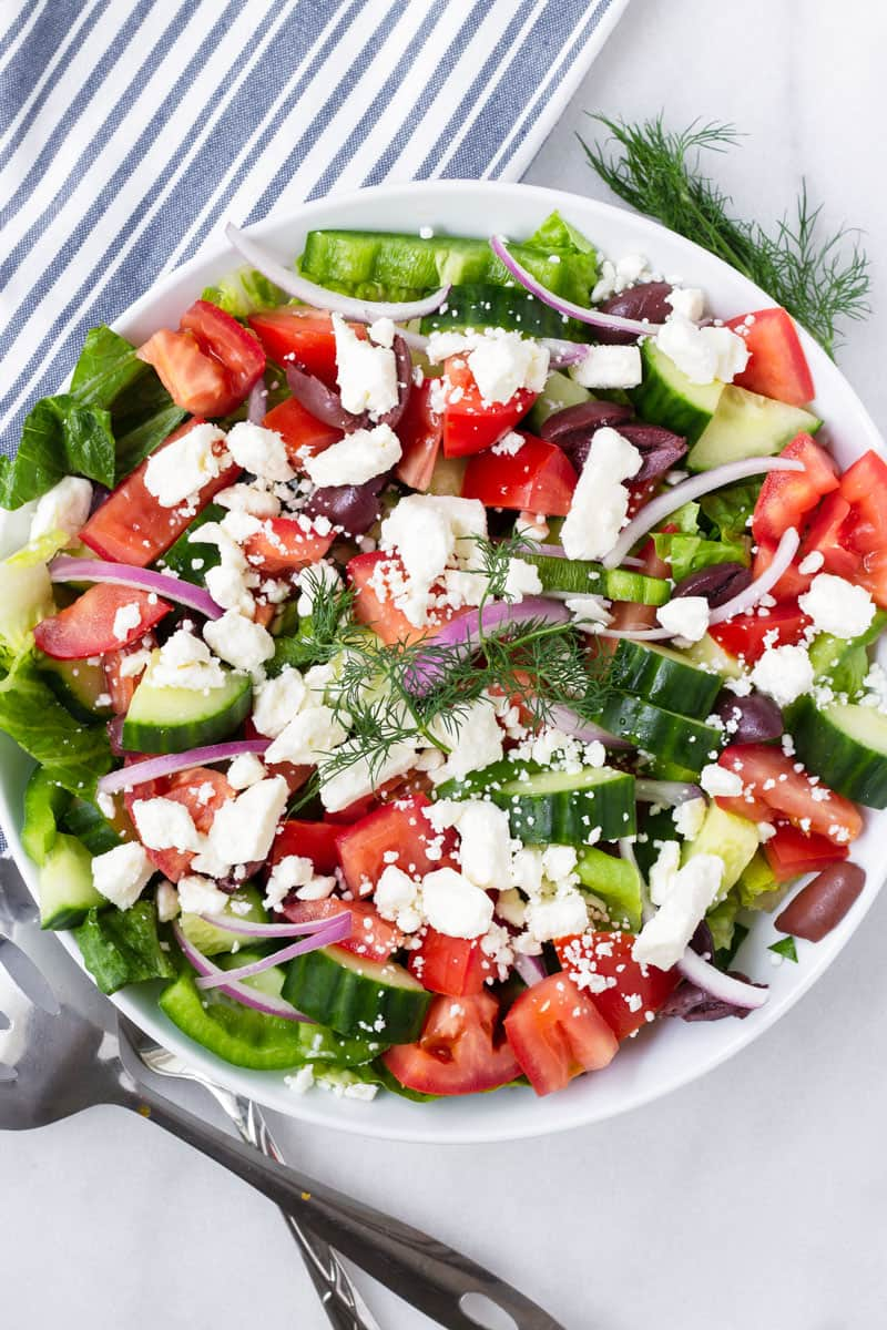 bowl with Greek salad on a striped white and blue napkin and serving spoons