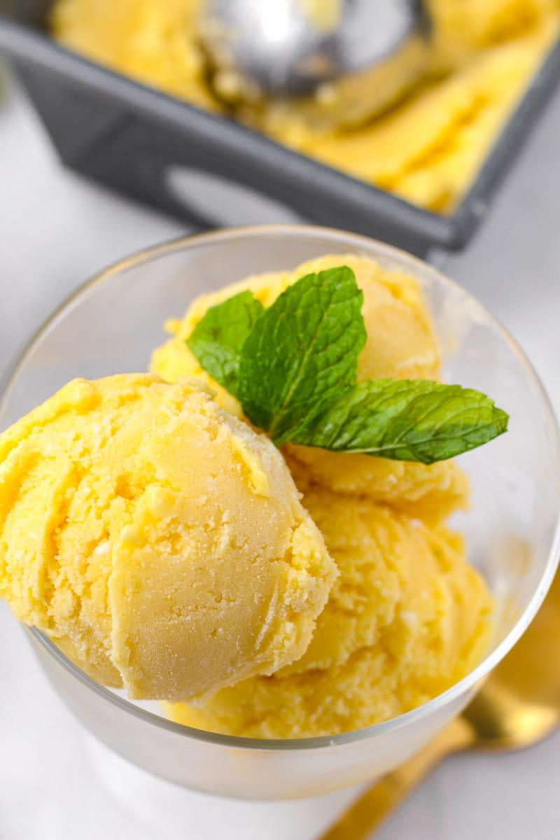 Close up of three scoops of mango ice cream with coconut milk and mint garnish