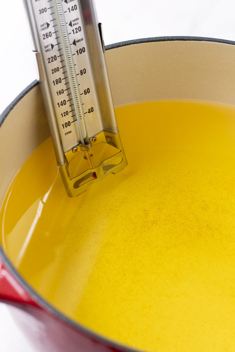 red cast iron put with oil and a candy thermometer