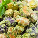 Close up of baby potato salad with pesto and basil leaves