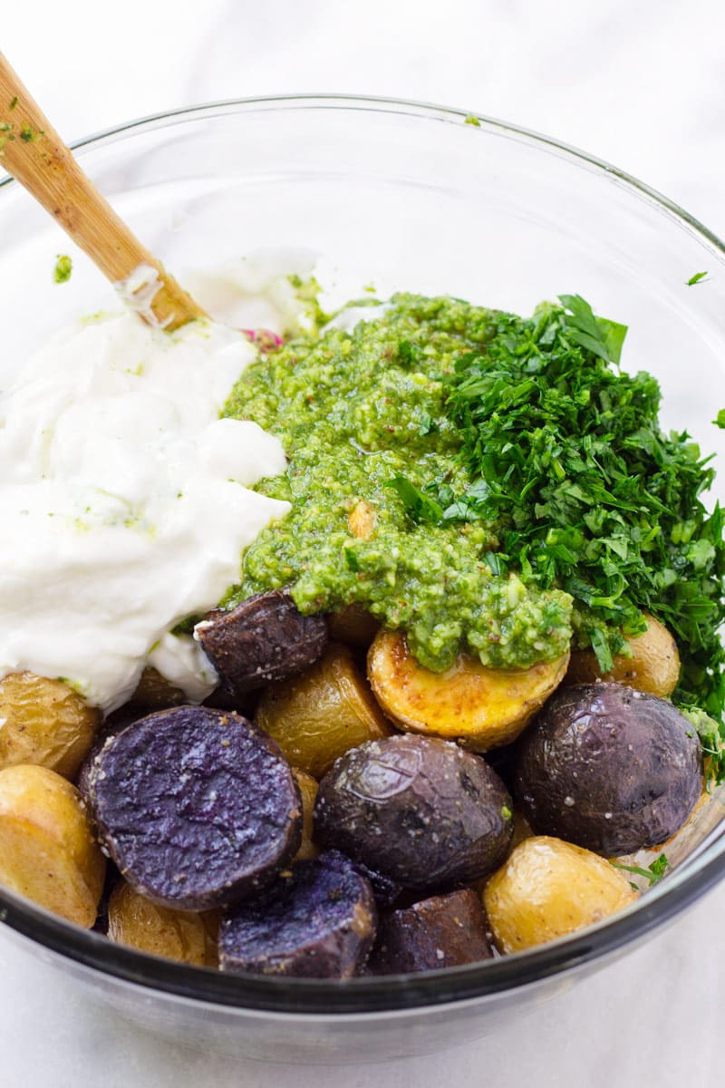 Purple and yellow roasted potatoes, parsley, pesto, yogurt and a wooden spoon