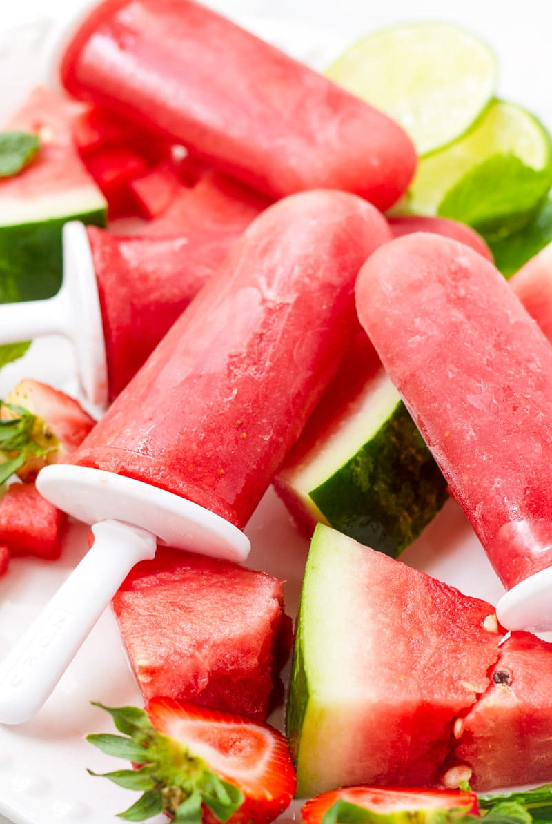 Homemade watermelon strawberry ice pops resting on cut up watermelon