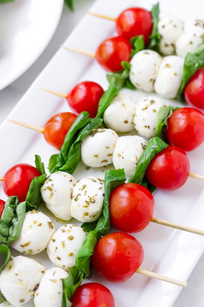 White rectangular plate with build caprese salad skewers