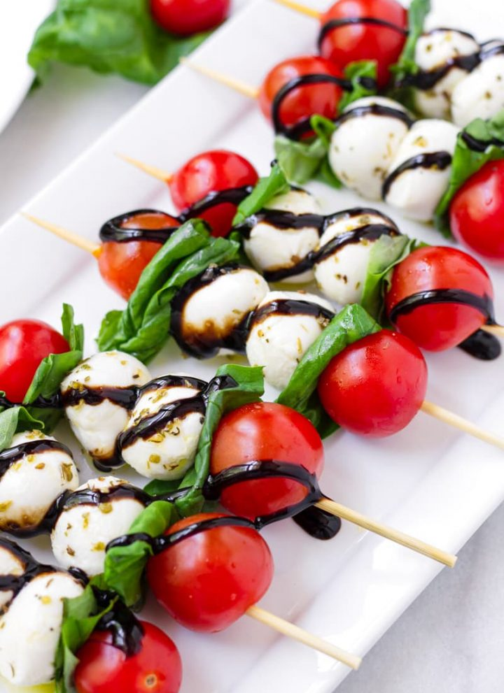 Close up of tomato, mozzarella, and basil skewers drizzled with balsamic