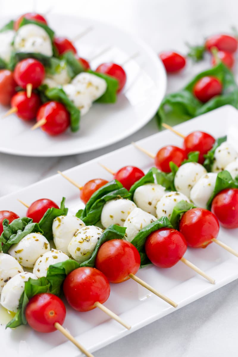 White rectangular platter with caprese skewers lined up