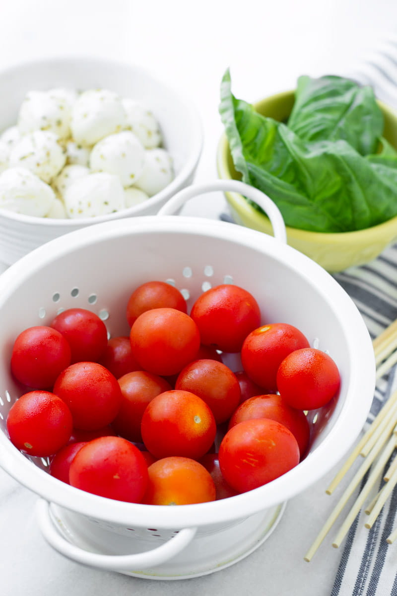 white colander with cherry tomatoes and basil and mozzarella cheese in the back