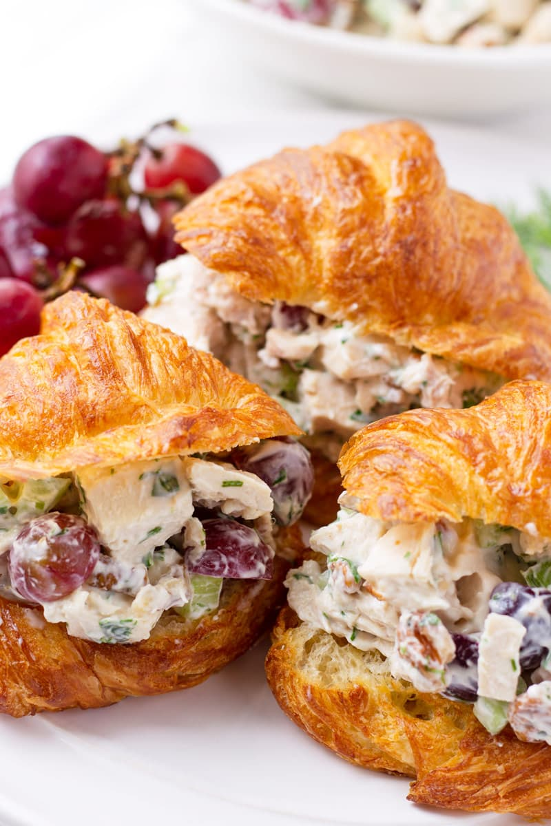 Three croissant sandwiches with creamy chicken salad and grapes