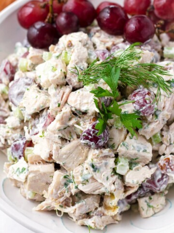 Close up of grape chicken salad with dill and parsley garnish