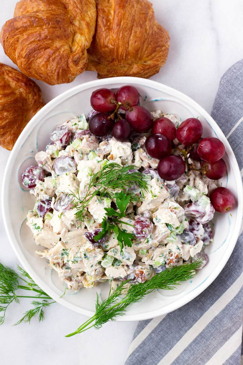 Top view of chicken salad with dill and grapes, and three croissants