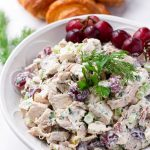 Round bowl with prepared mayo chicken salad and whole grapes