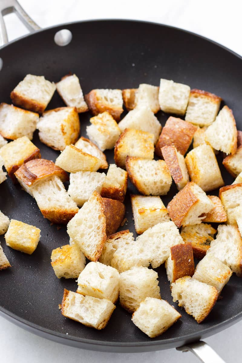 Large dark skillet with toasted bread cubes and olive oil