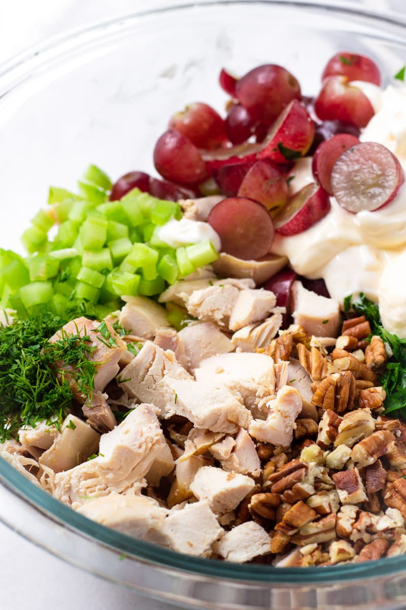 Bowl with celery, grapes, parsley, pecans, dill, and cubed chicken