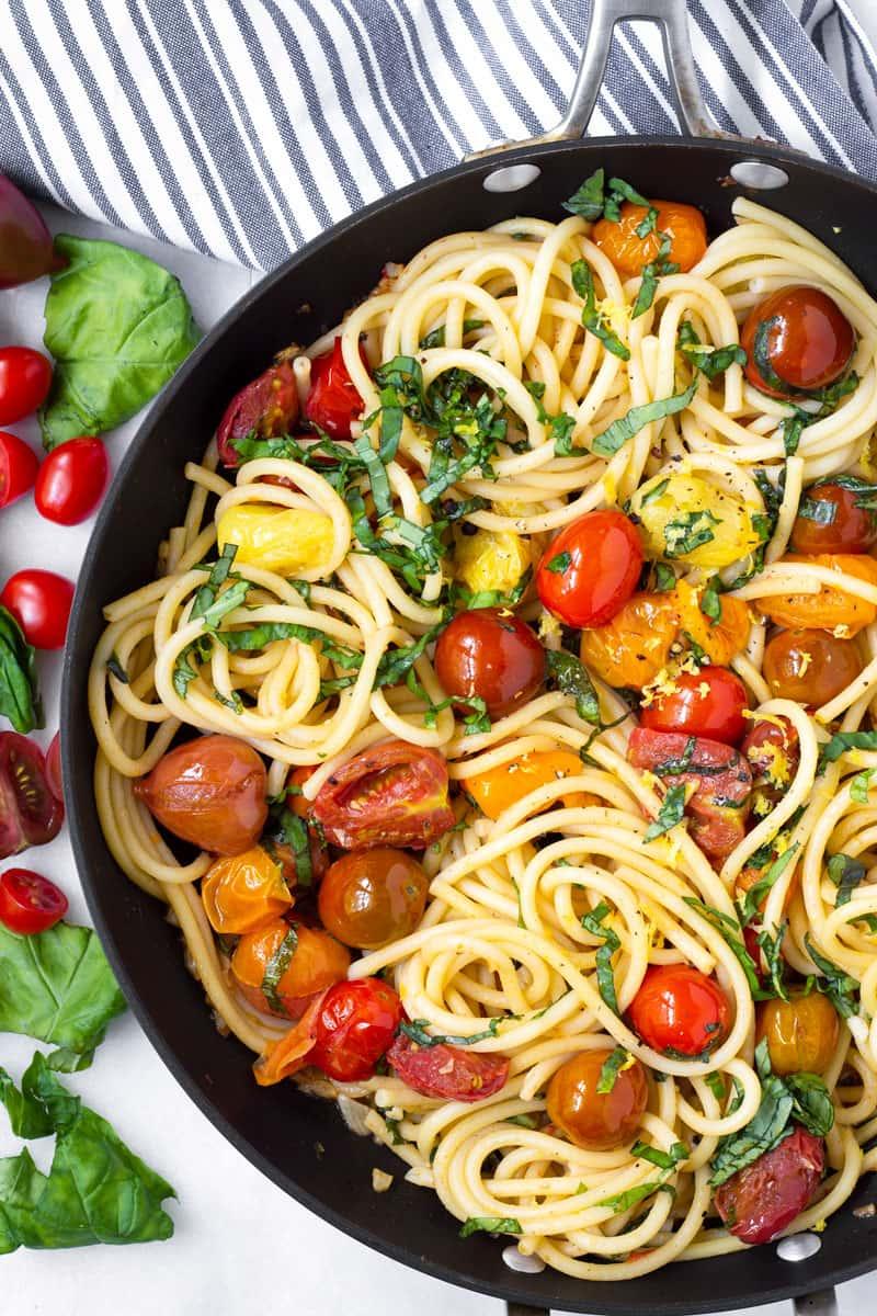 Top view of tomato, lemon, and basil bucatini