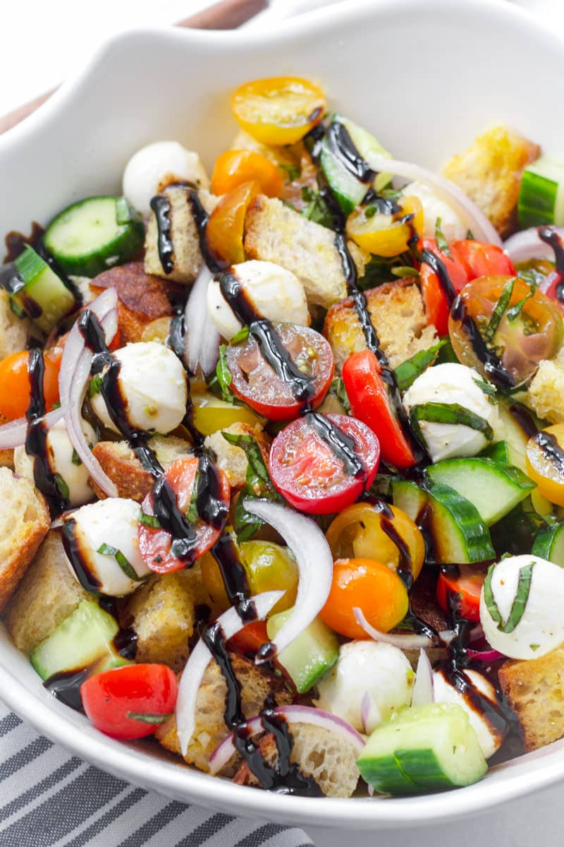Large bowl with classic panzanella salad drizzled with balsamic glaze