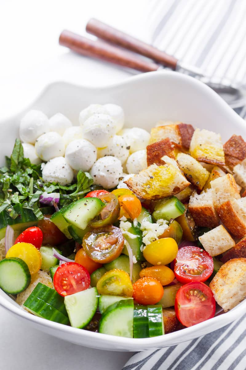 Large bowl with cucumbers, tomatoes, bread cubes, mozzarella, and basil